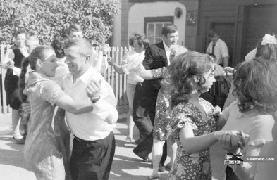 Участники свадьбы танцуют перед деревенским домом под звуки баяна