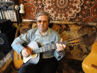 Александр Шеваловский у себя дома с гитарой