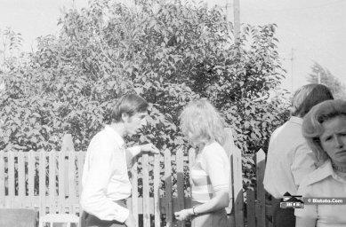 Гости советской свадьбы разговаривают у плетня