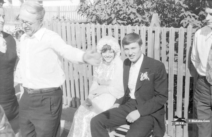 Жених с невестой сидят на деревенской лавочке