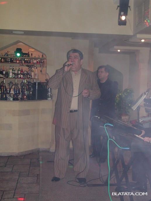 Бока Давидян с микрофоном на сцене ресторана поёт